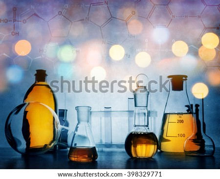 Test glass flask with solution in research laboratory. Science and medical background. Focus in the foreground. - stock photo