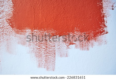 Test painting the blue wall with red color - stock photo