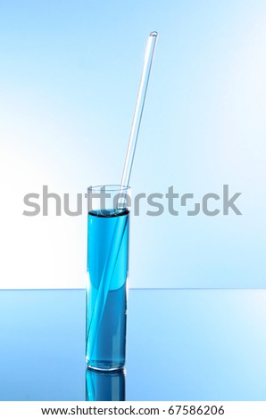 Test tube on blue background. With glass stick - stock photo