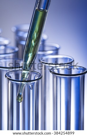 test tube with dropper on blue background - stock photo