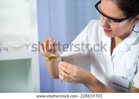 Test tube with urine sample in doctor hand - stock photo