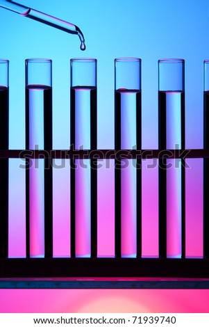 Test tubes and dropper against a colorful background