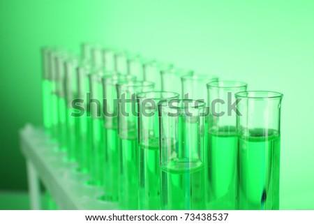 Test-tubes on green background - stock photo