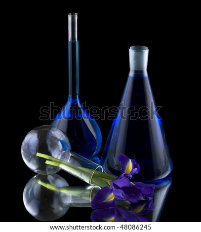 Test tubes with blue liquid and iris flowers
