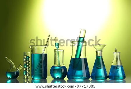 Test-tubes with blue liquid on green background