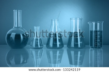 Test tubes with colorful liquids in green light - stock photo