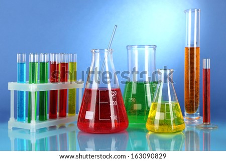 Test tubes with colorful liquids on blue background