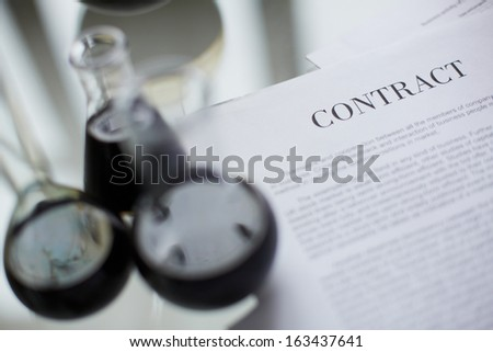 Test-tubes with liquid oil over paper agreement - stock photo