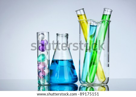 Test-tubes with liquid on gray background - stock photo