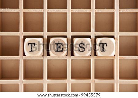 Test word construction with letter blocks / cubes and a shallow depth of field - stock photo