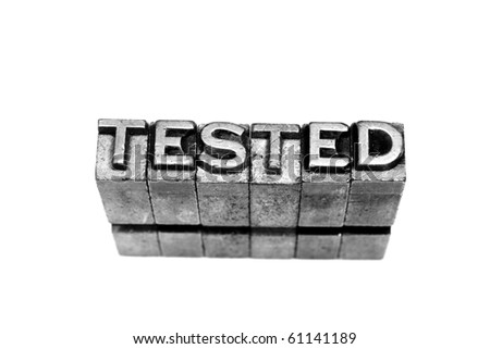 TESTED written in metallic letters on a white background - stock photo