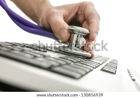 Testing a computer keyboard with stethoscope. - stock photo