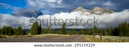 Teton Mountains, a fogbank, and the scenic byway from a turnout - stock photo