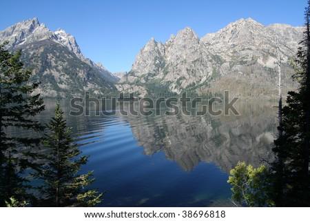 Teton Range, reflecting in deep blue Jenny Lake - stock photo