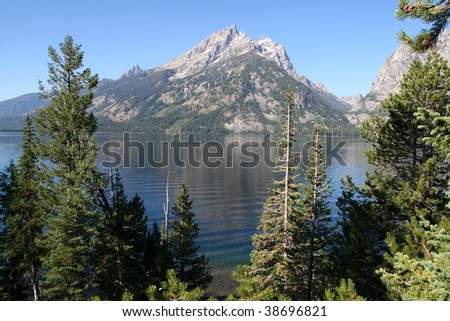 Teton Range, reflecting in deep blue Jenny Lake, with trees in the foreground - stock photo