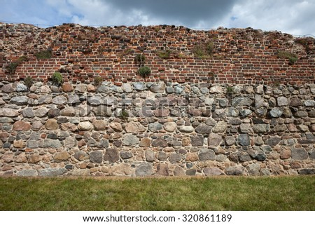 Teutonic Knights Castle wall background in Torun, Poland, stone and brick medieval fortification.