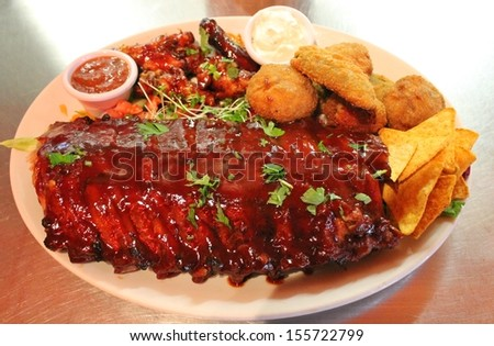 Tex mex BBQ ribs and wings platter with nachos - stock photo