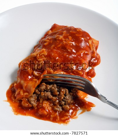 tex-mex beef enchilada, topped with spicy tomato sauce,with a fork. - stock photo