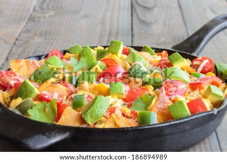 Tex-Mex breakfast migas made of eggs scrambled with onions, red bell pepper, jalapeno, cheese, topped with cherry tomatoes, avocado and cilantro - stock photo