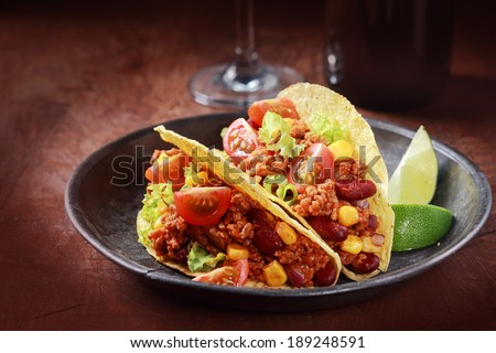 Tex-mex cuisine with a serving of two corn tacos with ground meat, salad and vegetable filling in a rustic wooden bowl with a garnish of lemon wedges - stock photo
