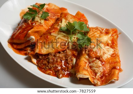 Texan/Mexican-style enchiladas, tortillas filled with spicy beef topped with grated cheese and tomato-chili salsa. - stock photo