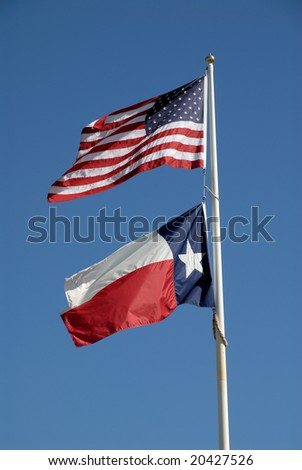 Texas and United States flags against blue sky - stock photo