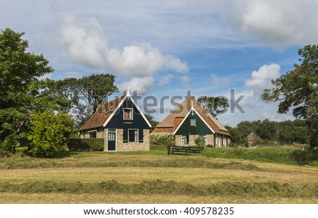 Texel, The Netherlands - August 23, 2012: Two typical houses of the Wadden isle with in front a meadow with hay and some trees.