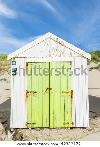 Texel, The Netherlands - August 23, 2012: White and green cabin on the beach on the isle of Texel.
