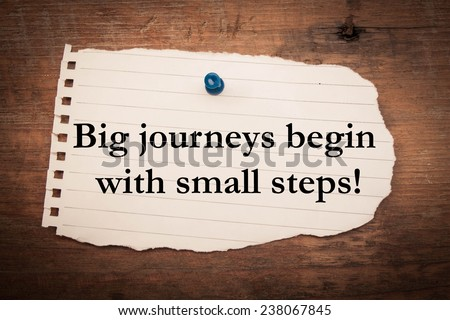 Text big journeys begin with small steps on note paper  - stock photo