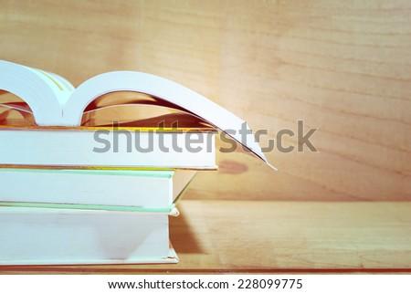Text books on wooden desk, vintage tone  - stock photo