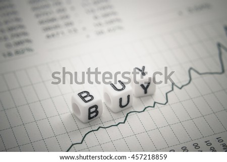 Text buy from letters cube on chart stock report, top view, soft focus
