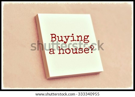 Text buying a house on the short note texture background - stock photo