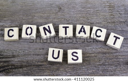 Text: Contact us from wooden letters on wooden background - stock photo