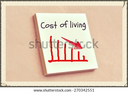 Text cost of living on the graph goes down on the short note texture background - stock photo