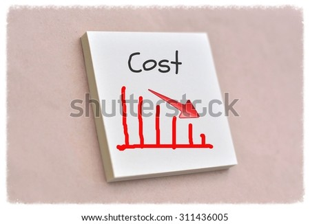 Text cost on the graph goes down on the short note texture background - stock photo