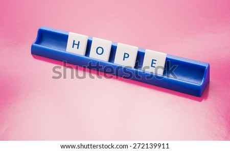 Text game tiles spelling the word hope. Conceptual image of belief, motivation and inspiration. - stock photo