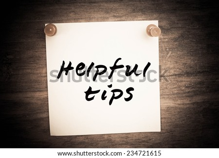 Text helpful tips on note paper and wood - stock photo