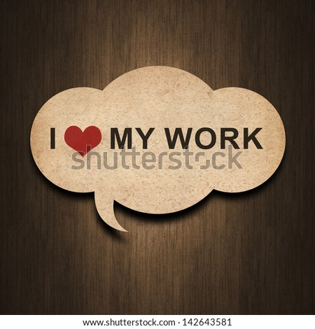 text i love my work on speech bubble paper on wood background - stock photo
