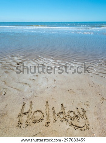text in the sand on the beach during the summer holidays - stock photo