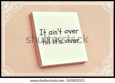 Text it ain't over till it's over on the short note texture background - stock photo
