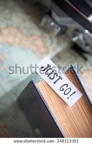 "Text ""Just go"" book and map. Travel and tourism concept. Vintage photo."