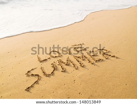 "Text ""love summer"" written in the sand on the beach with a wave."