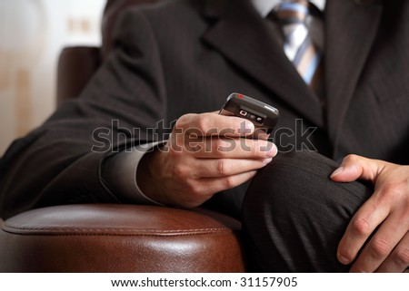 Text messaging or checking email on mobile phone whilst waiting for a business meeting