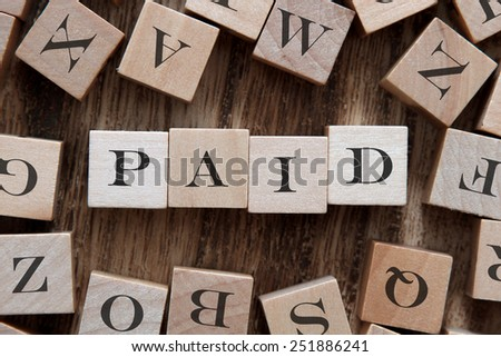 text of PAID on cubes - stock photo