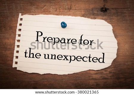 Text prepare for the unexpected on note paper and wood  - stock photo