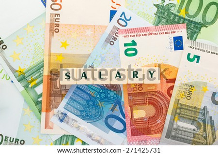 Text salary with background of several euro banknotes. Money of the european union. Word created with dice design. - stock photo