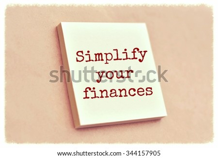 Text simplify your finances on the short note texture background - stock photo