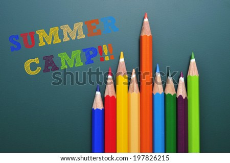 text summer camp written on a chalkboard and some colored pencils of different colors - stock photo