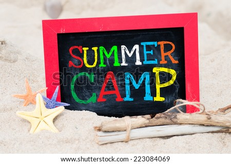 Text Summer camp written with chalk on chalkboard. Text Summer camp written with chalk on chalkboard, on sandy beach side  - stock photo