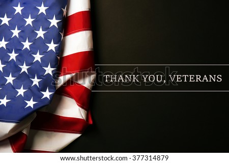 Text Thank A You, Veterans on black background near American flag - stock photo